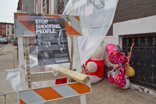 CeaseFire Philadelphia posts fliers at the site and memorial of a recent shooting in North Philadelphia. (Kimberly Paynter/For NewsWorks)