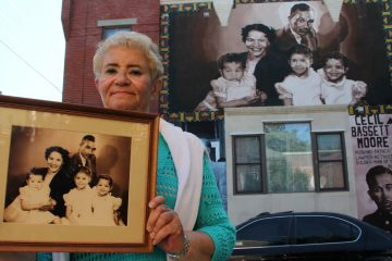 Cecily Banks, the oldest daughter of Cecil B. Moore, stands beside a mural honoring her father at the corner of West Jefferson and North Bouvier streets. (Emma Lee/WHYY)