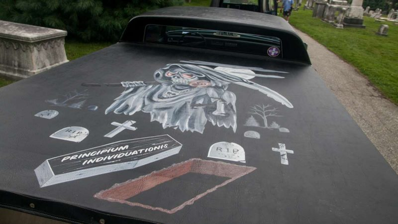 A grim reaper painting is seen on the cover of a modified Cadillac hearse with the rear section of the roof removed and converted into a truck bed. (Brad Larrison for NewsWorks)