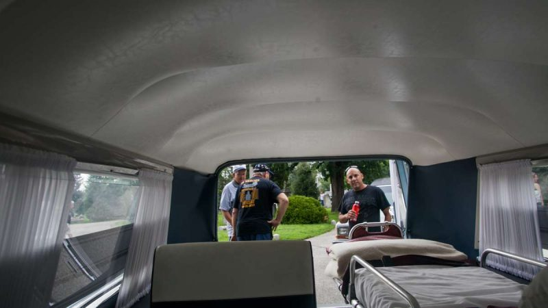Visitors inspect he interior of a 1963 S & S Cadillac Park Row combination car that doubled as an ambulance and a hearse. (Brad Larrison for NewsWorks)