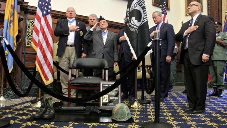 Medal of Honor recipients (front row from left) Mike Thornton and Hershel ''Woody'' Williams salute during the unveiling  ceremony for a Chair of Honor in the Mayor's Reception Room at City Hall. (Emma Lee/WHYY)