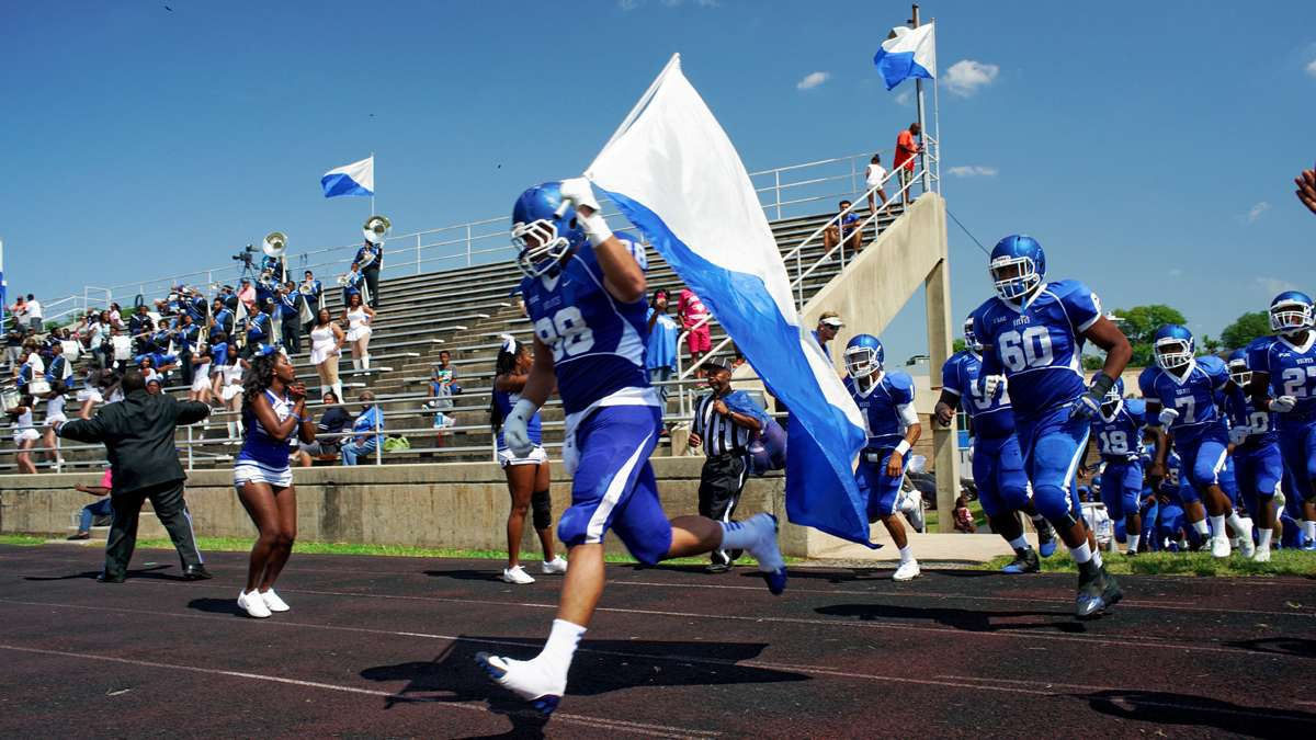 Senior Christian Sanchez caries the flag as the Cheyney University Wolves enter O'Shields-Stevenson Stadium for the 'Battle of the Firsts' against Lincoln University Lions. Cheyney is the country's oldest institution of higher learning for black students, while Lincoln was the first one to grant degrees. (Bastiaan Slabbers/for NewsWorks)
