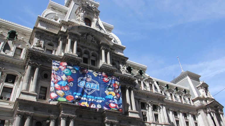 A banner touting the NFL draft hangs on the east side of City Hall. (Emma Lee/WHYY)