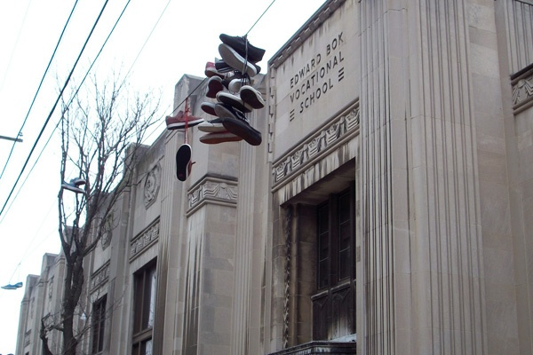 A familiar sight in South Philadelphia, shoes are flung up to hang from power lines in front of Edward Bok High School, at 9th and Mifflin streets. (Eric Walter/WHYY)