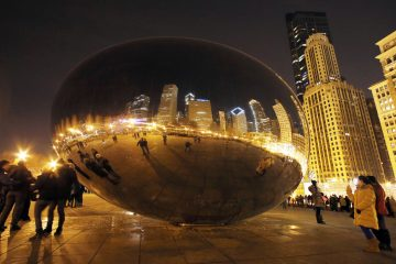People enjoy the Cloud Gate sculpture, also known as 'The Bean' in Millennium Park in Chicago.  (AP Photo/Nam Y. Huh)