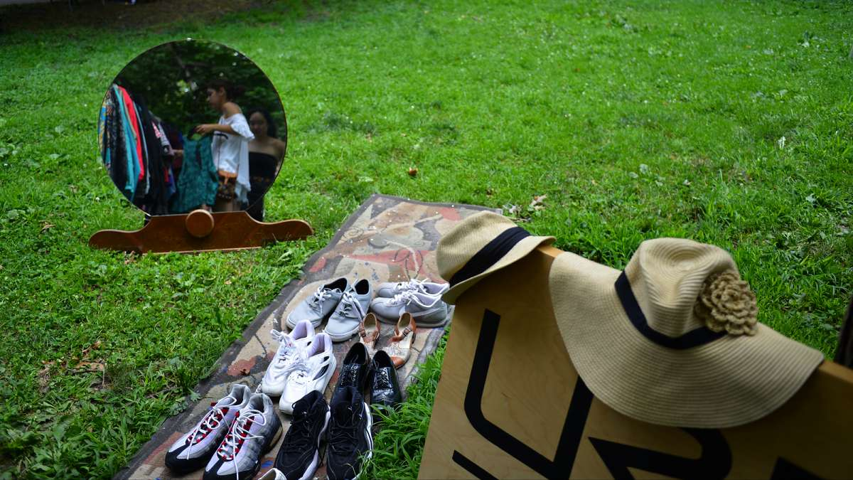 A mirror on the grass reflects a scene at one of the vendors during the annual Clark Park Festival in West Philadelphia