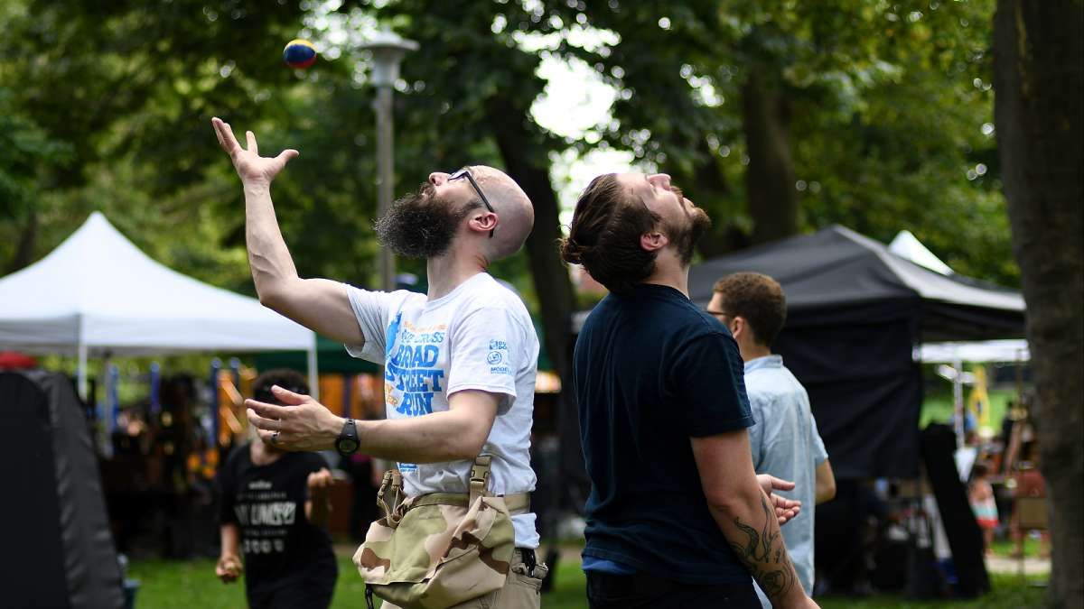 Christian Johnson, of East Mt Airy and Ken Haines, of Manayunk share some skills as they practice a juggling routine under the trees during the annual Clark Park Festival
