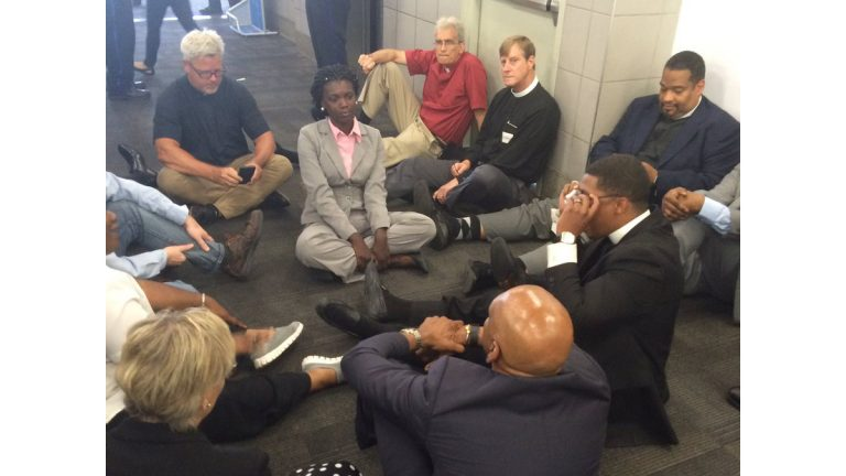 Members of the clergy stage a sit-in at Philadelphia International Airport (photo via <a href=
