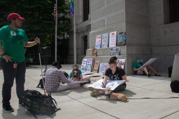Protesters prepare signs before a rally outside of Philadelphia City Hall to recognize transgender people of color in the LGBTQ movement. (Emily Cohen for NewsWorks).