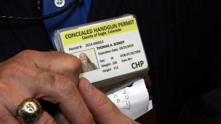 A Colorado man shows his concealed gun license. AP Photo/Brennan Linsley, file)