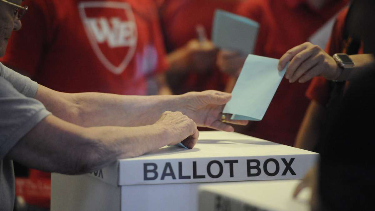 A member of the Philadelphia teachers union hands in a ballot Monday night at Temple University's Liacouras Center as the Philadelphia Federation of Teachers voted on a contract proposal. The plan that runs through 2020 won overwhelmingly.