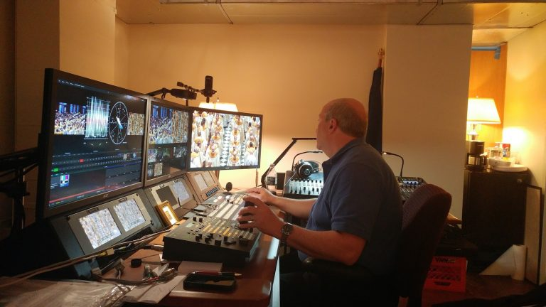 Dan Kerns operates robotic cameras at the 'cathedral control room,' located behind the altar. (Tom MacDonald/WHYY)