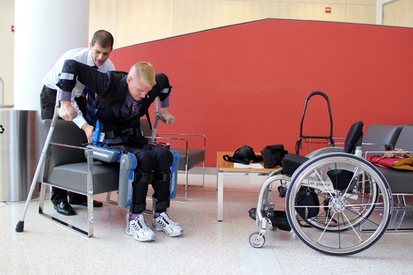 Pierre Asselin assists medical student and Air Force veteran Ian Brown to stand for photos using an exoskeleton that allows paraplegics to walk. (Emma Lee/for NewsWorks)