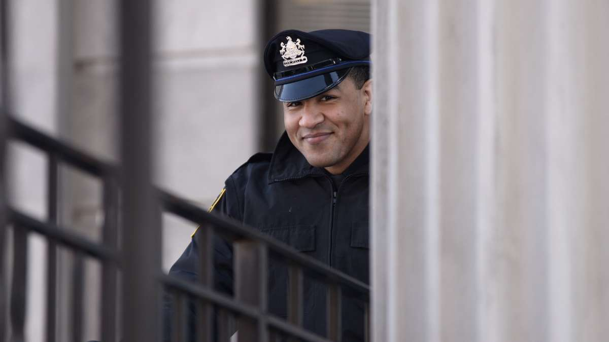 A police officer smiles from behind a column at the Montgomery County Courthouse.