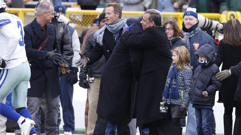 New Jersey Gov. Chris Christie, center right, embraces a person on the sidelines before an NFL divisional playoff football game between the Green Bay Packers and Dallas Cowboys Sunday in Green Bay, Wis. (AP Photo/Mike Roemer)