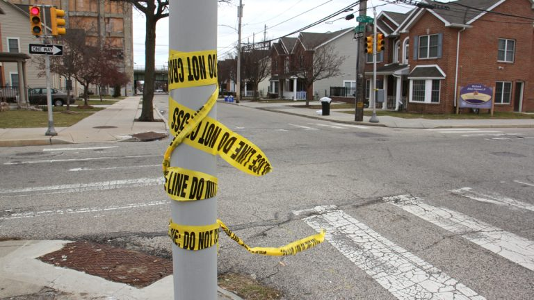 Crime scene tape remains at the intersection of 10th and Poplar streets where police subdued a man who later died. (Emma Lee/WHYY)