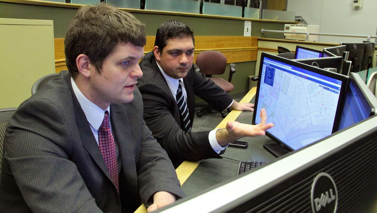 Philadelphia police data experts Kevin Thomas (left) and Anthony D'Abruzzo review data at the Crime Analysis Lab at police headquarters.