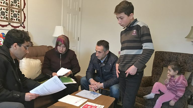 Amer Alfayadh, caseworker for Church World Service's Lancaster office, reviews paperwork with Marwa Hilani, her husband Imad Ghajar and children Mohamad, 14, and Lamar, 4. (Emily Previti/WITF)