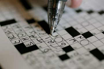 A puzzle fan works on the New York Times crossword puzzle in pen at the