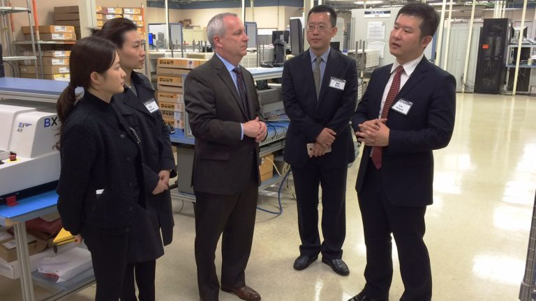 David Burt (center), a CTDI  vice president, explains the company's operations to a delegation from China at the company's West Goshen facility last year. CTDI currently does business at 13 locations throughout China. (Chester County commissioners office)