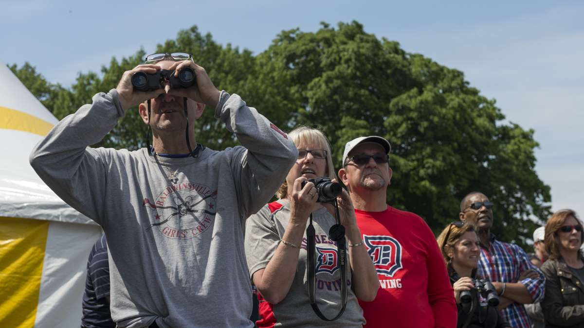 Eric Hughes takes in the action through his binoculars from a seat along the Schuylkill River.