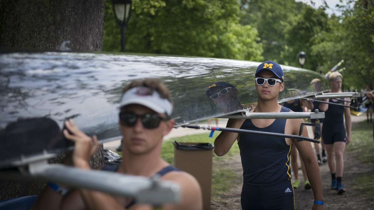 Athletes carry their boat toward the Schuylkill River for the competition.