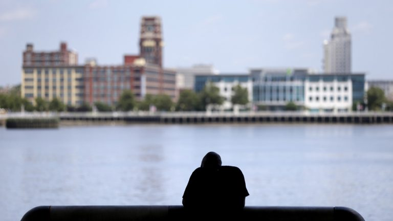 A man rests in the shade along the Delaware River in Philadelphia. (AP Photo/Matt Rourke, file)