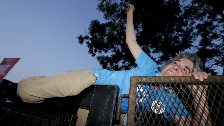 A protester climbs over the fence near the AT&T Station in Philadelphia