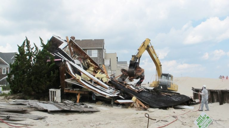 Workers tear down Rich Hennion's home in Normandy Beach that was damaged beyond repair by Superstorm Sandy (Phil Gregory for NewsWorks).
