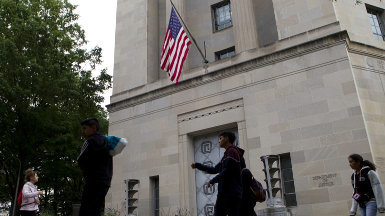 People walk outside the U.S. Department of Justice on Saturday, May 13, 2017. Attorney General Jeff Sessions and his deputy, Rod Rosenstein, interviewed several candidates to succeed ousted FBI Director James Comey at Justice Department headquarters on Saturday. (AP Photo/Jose Luis Magana)