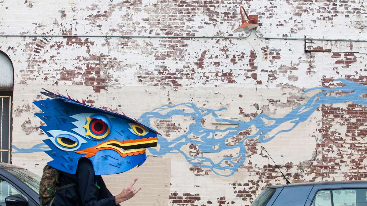 Rob Leef, wearing a dragon mask in the Kinetic Sculpture Derby appears to be breathing the blue flames painted on the brick wall behind him
