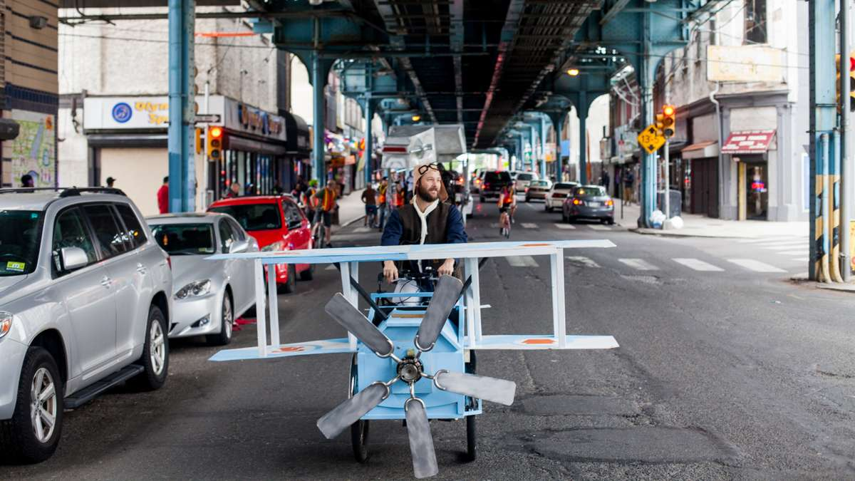 A man pilots a kenetic sculpture shaped like a biplane pedals down Front Street