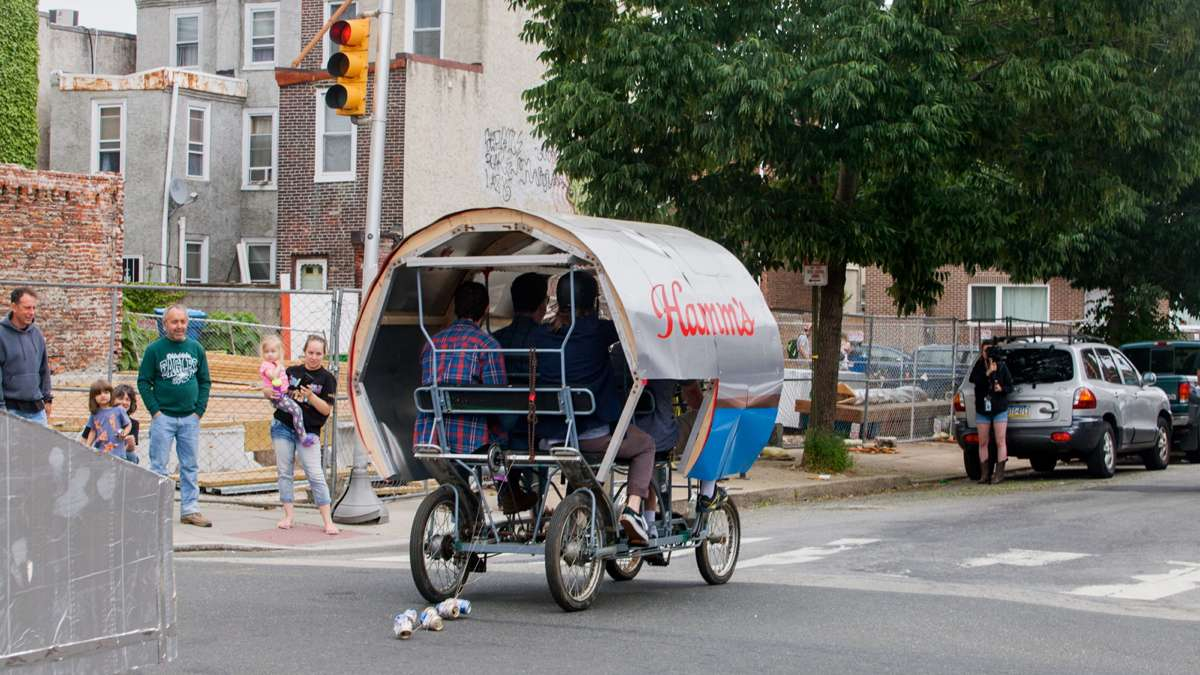 The Hamm's-Sters team pedal their oversize Hamm's beer can through Fishtown