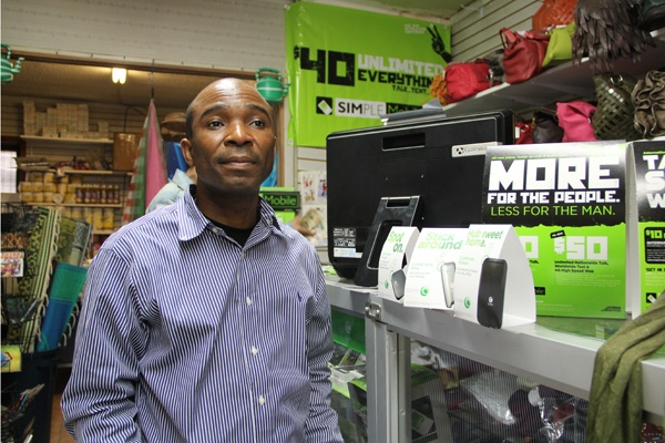 <p>Bakayoko Ben Hassan sells mobile internet devices at his shop on Woodland Avenue. (Emma Lee/for NewsWorks)</p>