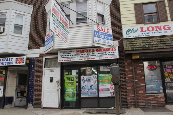 <p>Bakayoko Ben Hassan does a lot of business selling smartphones and other mobile internet devices at his shop on Woodland Avenue. (Emma Lee/for NewsWorks)</p>