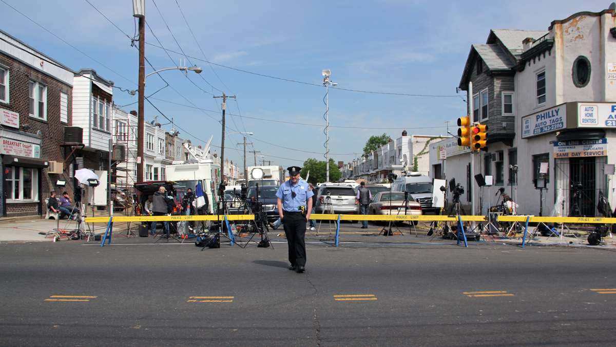 Police keep Frankford Avenue open by restraining media behind barricades on East Pike Street.