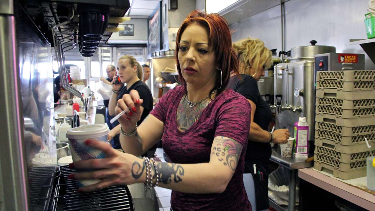 Waitress Erin Young and her coworkers keep up a frantic pace as the Clown House's regular customers are joined by members of the media and emergency workers.