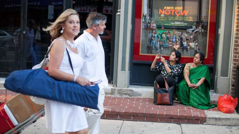 Bystanders on Arch Street watch the parade of white clad people on their way to Dîner en Blanc at Franklin Square Park. (Brad Larrison for NewsWorks)
