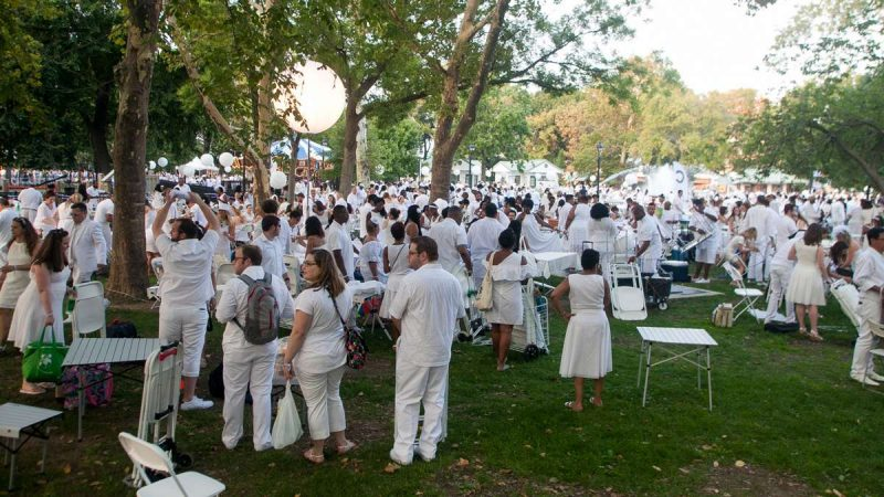 Franklin Square fills as participants in the annual Dîner en Blanc set up their tables on the grass. (Brad Larrison for NewsWorks)