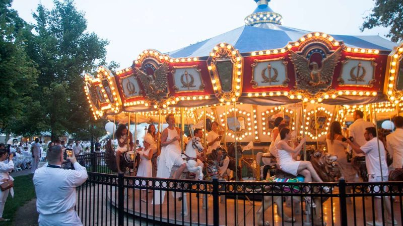 Diners ride the carousel in Franklin Square Thursday evening during the sixth annual Dîner en Blanc. (Brad Larrison for NewsWorks)