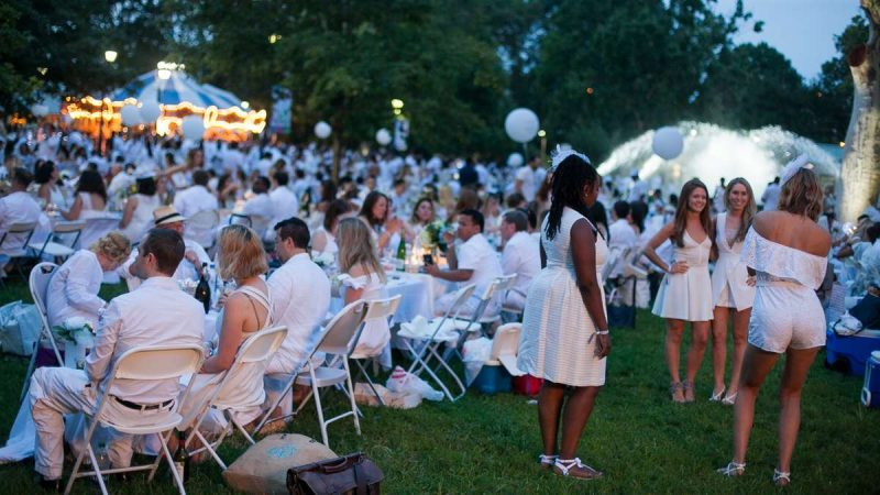 As evening deepens and lights come up, participants in the sixth annual Dîner en Blanc take time for photos. (Brad Larrison for NewsWorks)