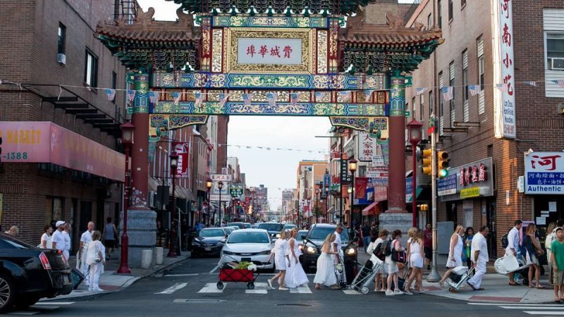 Thousands of people dressed in white, carrying their food and furniture, parade through Chinatown on their way to Dîner en Blanc at Franklin Square Park. (Brad Larrison for NewsWorks)