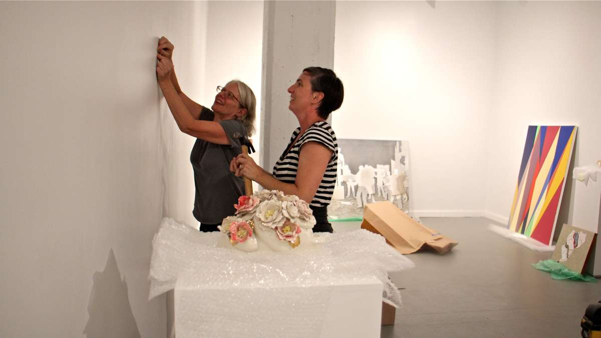 Jane Irish (left) and Mary Henderson of Tiger Strikes Asteroid galleries set up a show at the Crane Arts Building, their first since a fire displaced them from the Vox building on North 11th Street. (Emma Lee/WHYY)