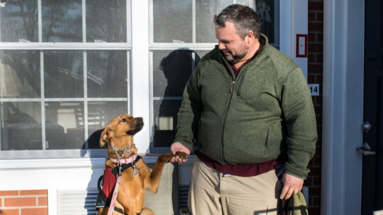 Russel Keyser shaking hands with his service dog, Artemis. (Paige Pfleger/WHYY)
