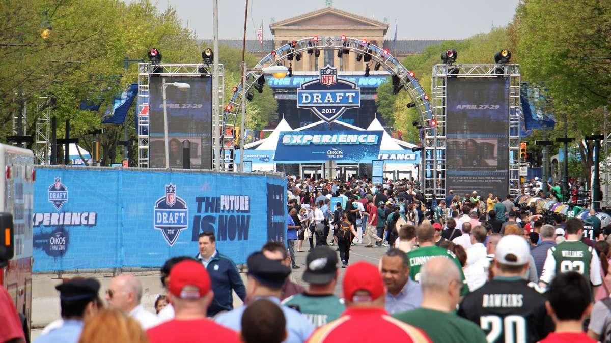 Crowds at the NFL Draft Experience stroll the Benjamin Franklin Parkway on the first day of the NFL Draft in Philadelphia, Pa. (Emma Lee/WHYY)