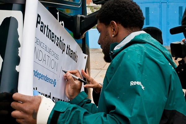 Philadelphia Eagles Player Akeem Jordan autographs a banner for Wister School on Tuesday after the Eagle Eyes Mobile made a stop to give eye checkups to uninsured or under-insured students. (Brad Larrison/for NewsWorks)