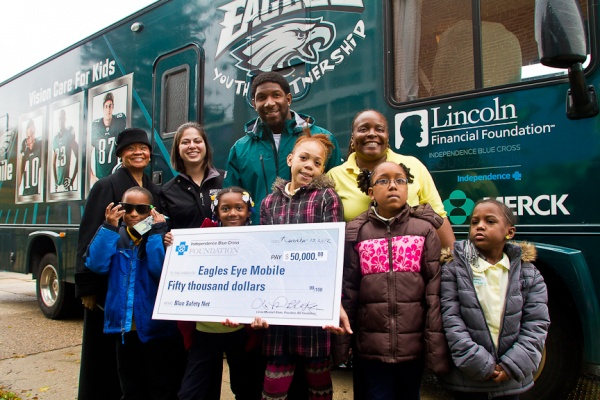 <p><p>Students from Wister School pose for a picture with Akeem Jordan of the Philadelphia Eagles and Lorina L. Marshall-Blake of Independence Blue Cross. (Brad Larrison/for NewsWorks)</p></p>