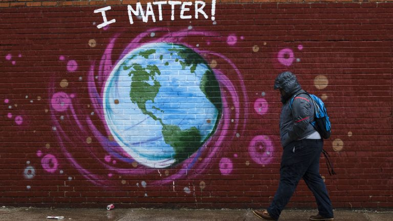 A man walks past a mural the day before Earth Day, in Philadelphia, Friday, April 21, 2017. (AP Photo/Matt Rourke)