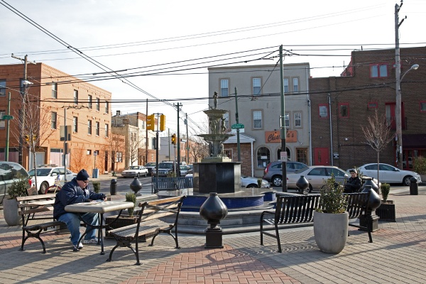 Vincent Orme (left) reads the South Philly Review at the fountain at Tasker Street and East Passyunk Avenue. (Lindsay Lazarski/WHYY).