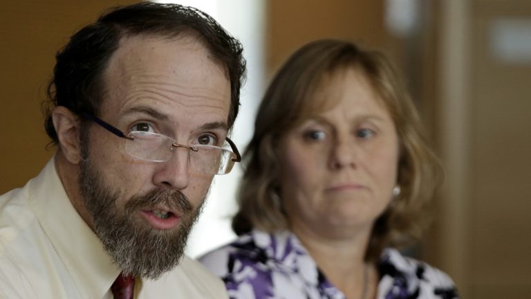 Dr. Rick Sacra, an American doctor who contracted the Ebola virus in Africa  and his wife, Debbie Sacra, address reporters during a media availability at the University of Massachusetts Medical Schoolin September. (AP Photo/Stephan Savoia)